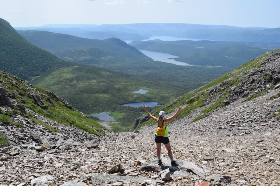 Photo shows a view from near the top of Gros Morne: hills, trees, and water. A woman stands back-on to the camera with her arms raised.